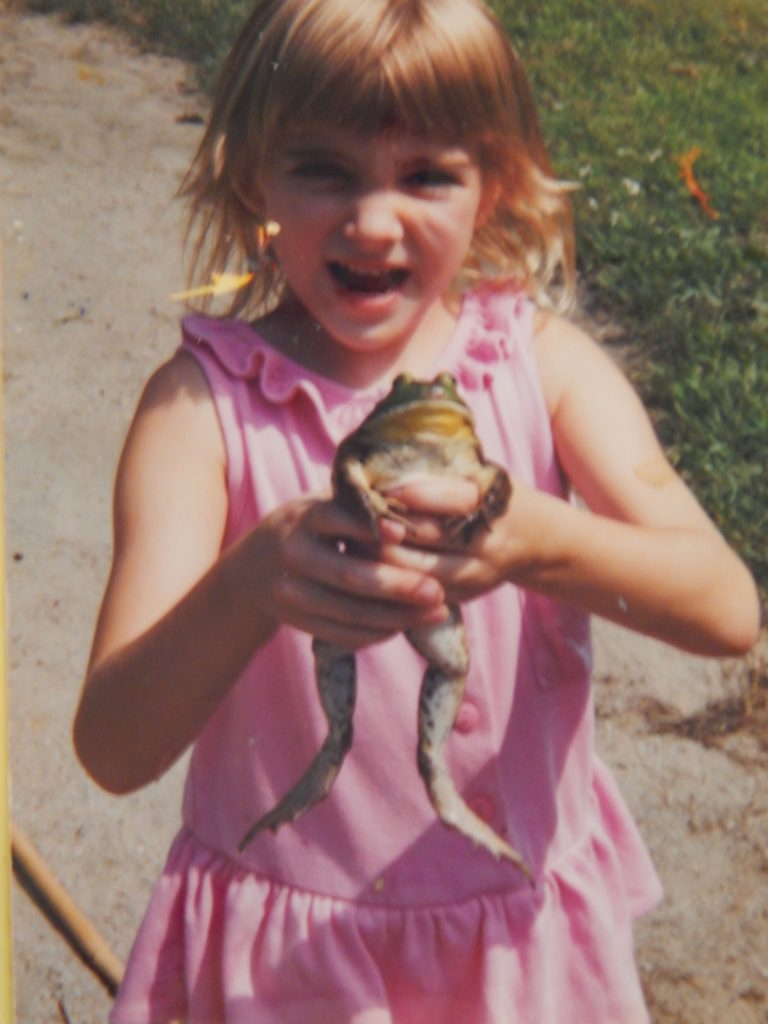 little girl in a pink ruffled shirt smiling proudly as she holds a large bull frog caught in the pond