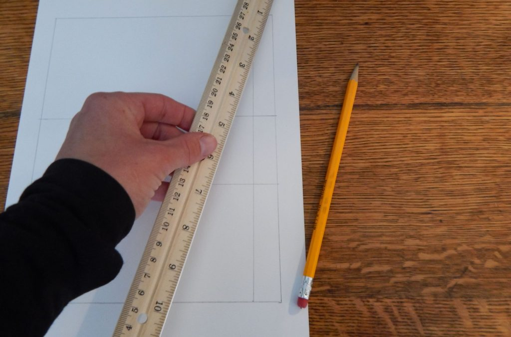 close up of a hand holding a ruler above white paper with a pencil on a wooden desk while making a compare and contrast