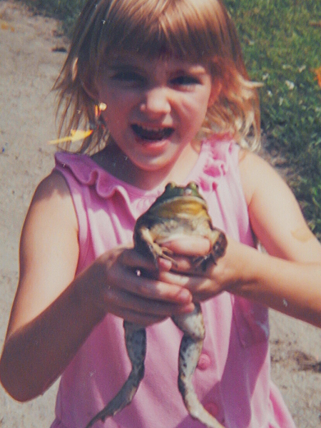 Julie as a young child wearing a pink ruffled tank top holding a large bull frog caught in the pond happy and proud expression on her face
