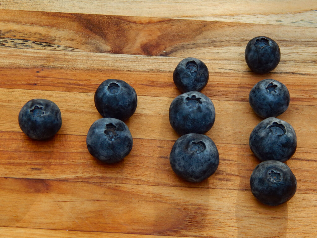10 blueberries sorted into number groups on a wooden board by a preschooler