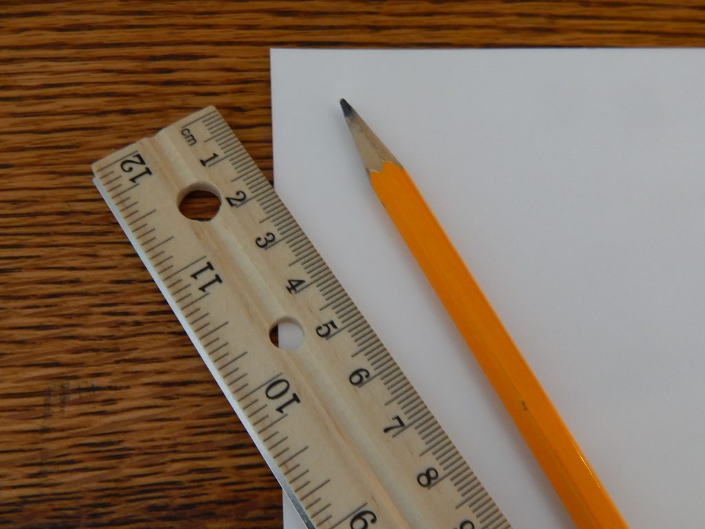 pencil and a ruler on a blank piece of paper on a wooden surface