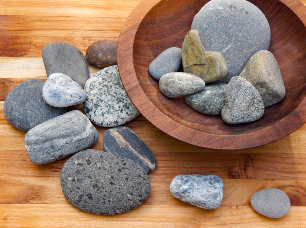 sorting bin with river and beach rocks in a wooden bowl variety of shapes, sizes, and patterns
