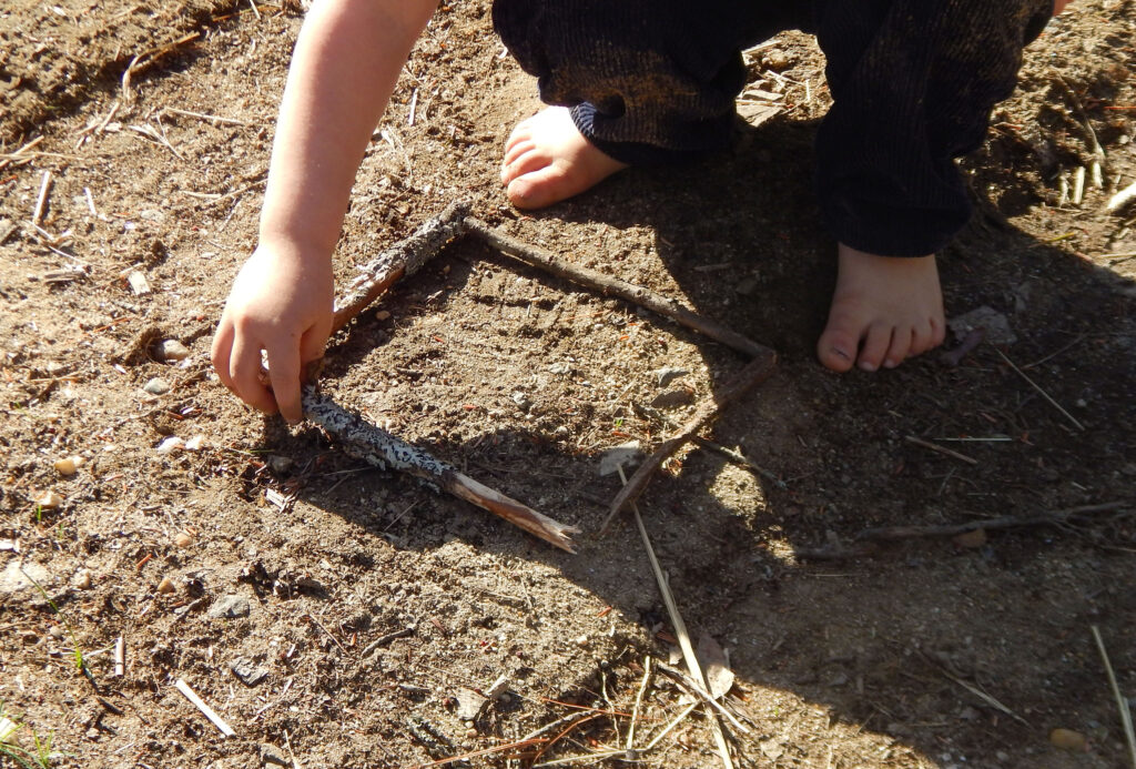 toddler creating a square outside using sticks on the dirt