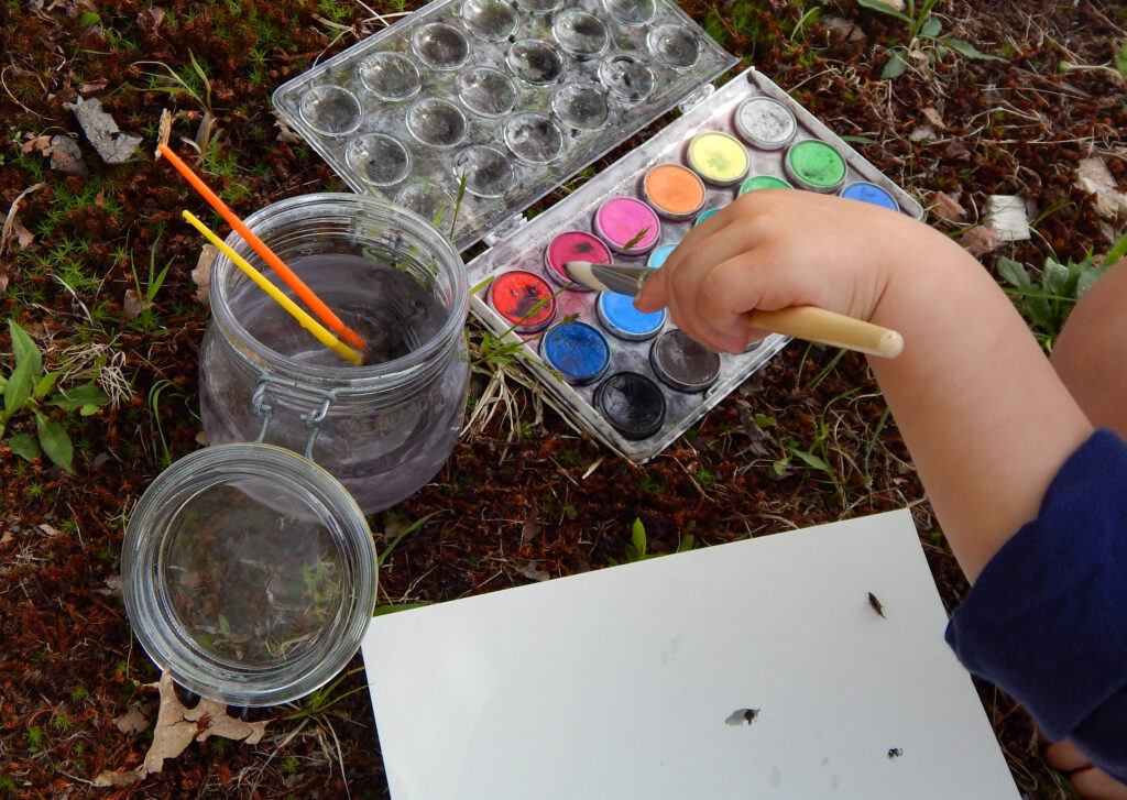 toddler painting outside holding a paint brush