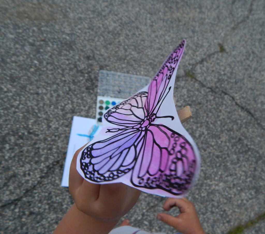 toddler holding butterfly craft outside
