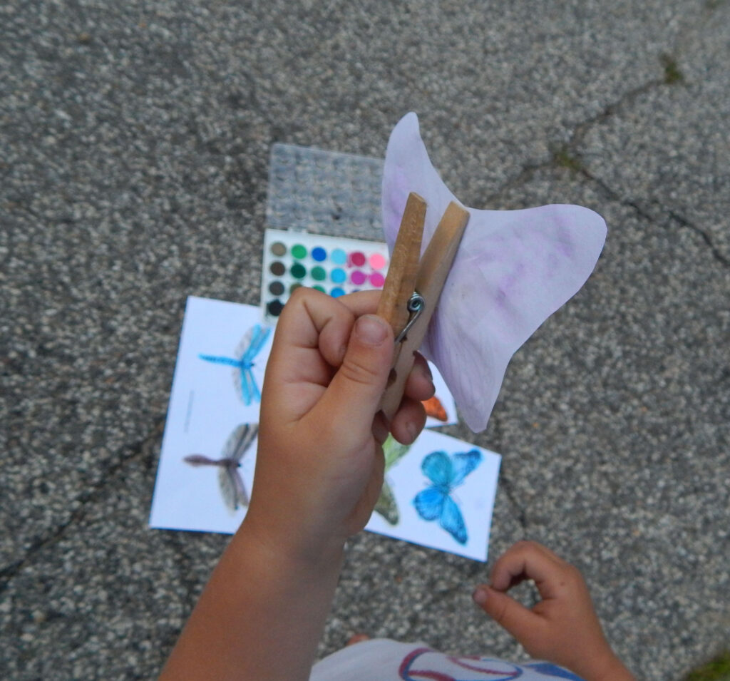 toddler holding a butterfly craft in driveway