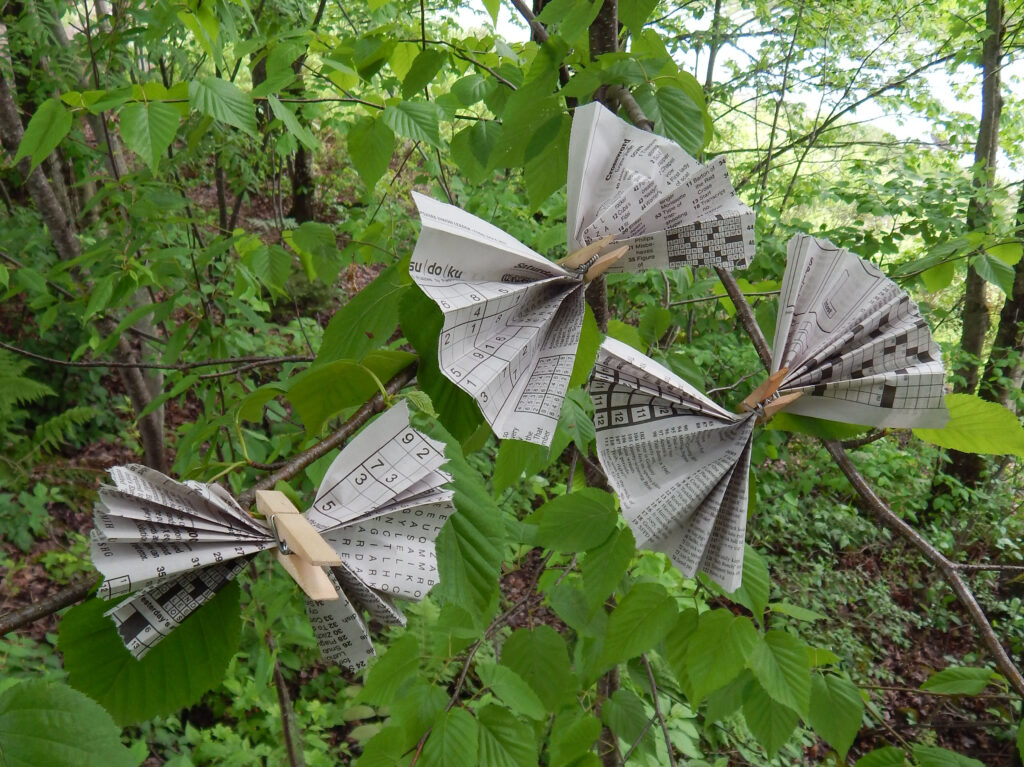 newspaper butterflies summer craft attached to trees with green leaves