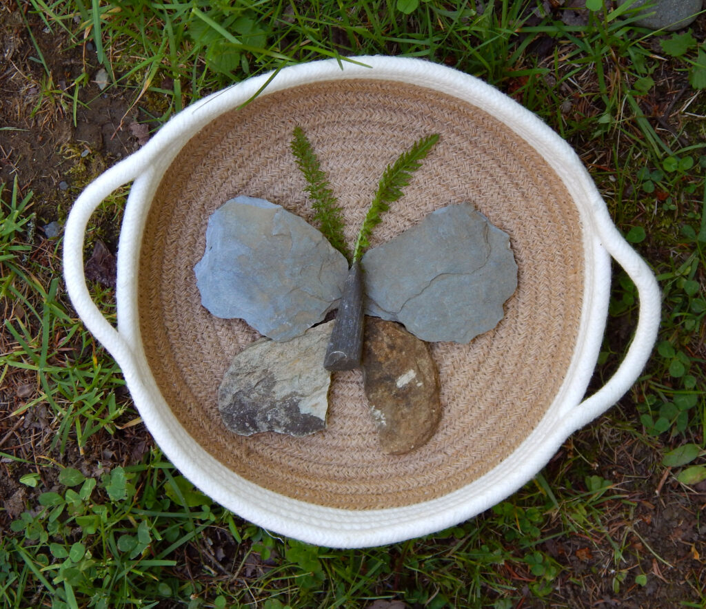 simple butterfly craft made out of rocks in a woven basket