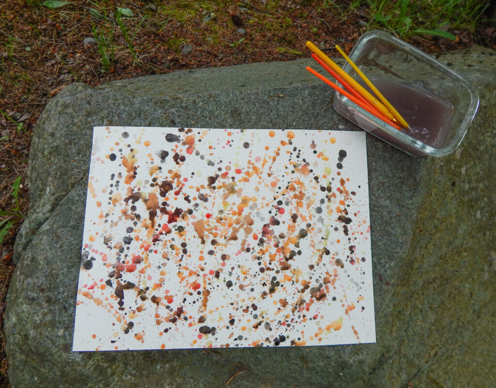 splatter paint paper in monarch butterfly colors orange, yellow, and black on a rock with paint brushes