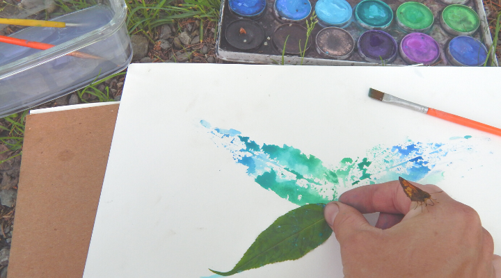 hand about to lift up a leaf butterfly leaf printing with watercolor paints outside