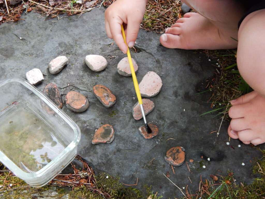 toddler hand with bare feet painting a rock with a paint brush outside craft project