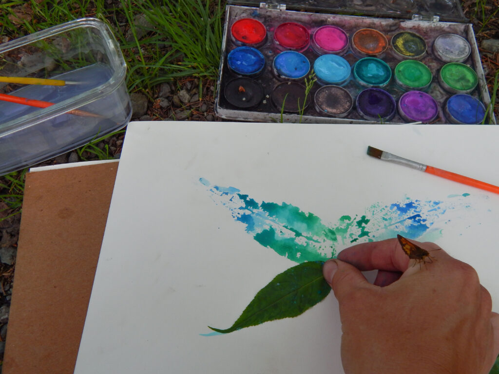 butterfly on girl's hand as she makes a print with leaves and watercolor paint paint supplies on ground brushes and water dish