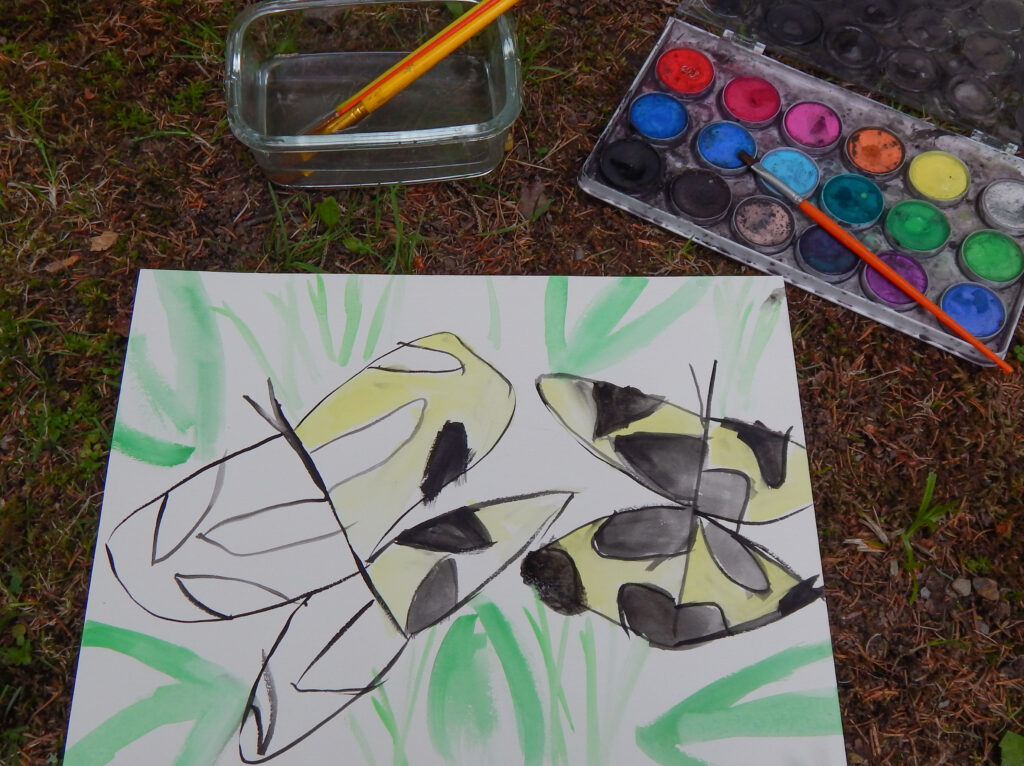 abstract swallowtail butterfly painting with art supplies outside on the ground