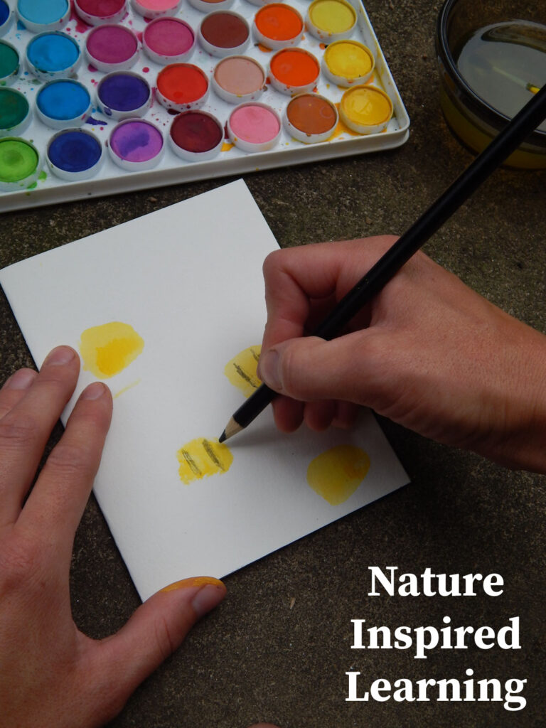 hand holding a black colored pencil adding stripes to bumble bee thumb print greeting card craft water color paint set above card