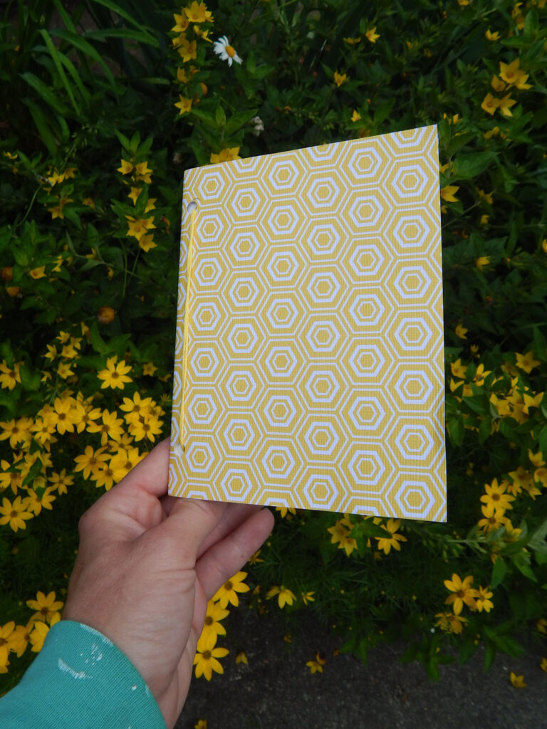 hand holding up a homemade DIY journal with yellow honeycomb cover outside in garden with yellow flowers