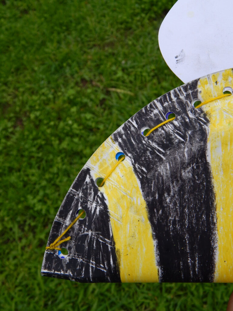 close up of a completed paper plate bee craft for kids folded in half and held together with yellow embroidery floss strung through holes green grass in background