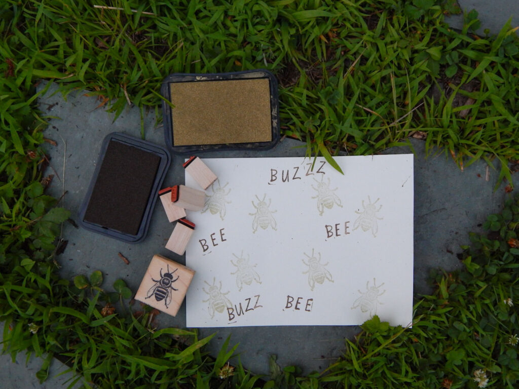 stamped bees in gold with stamped bee and buzz in dark brown on a paper outside on stepping stone with grass easy bee craft for kids