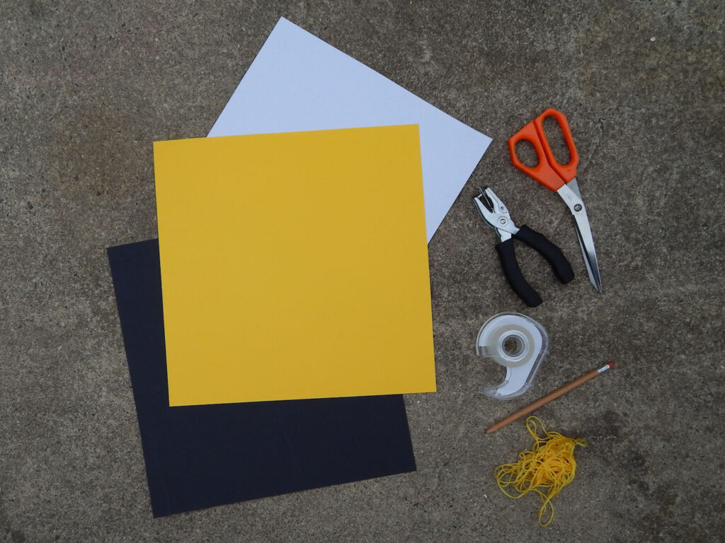 bumble bee craft supplies black white yellow construction paper, orange scissors, hole punch, tape, pencil, and yellow embroidery floss on cement