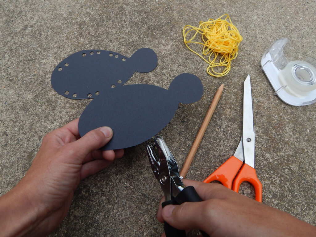hand holding bee's body with other hand hole punching for weaving craft supplies on ground