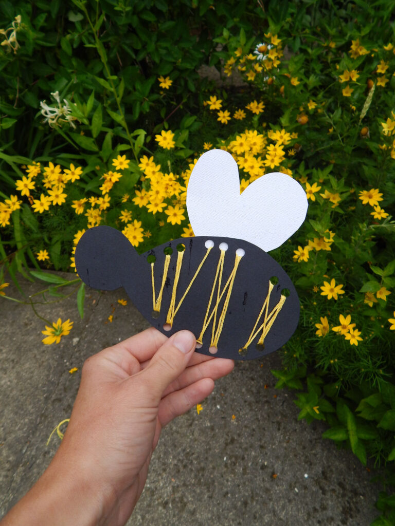 hand holding a DIY handmade bee craft for kids outside in the garden yellow flowers in background