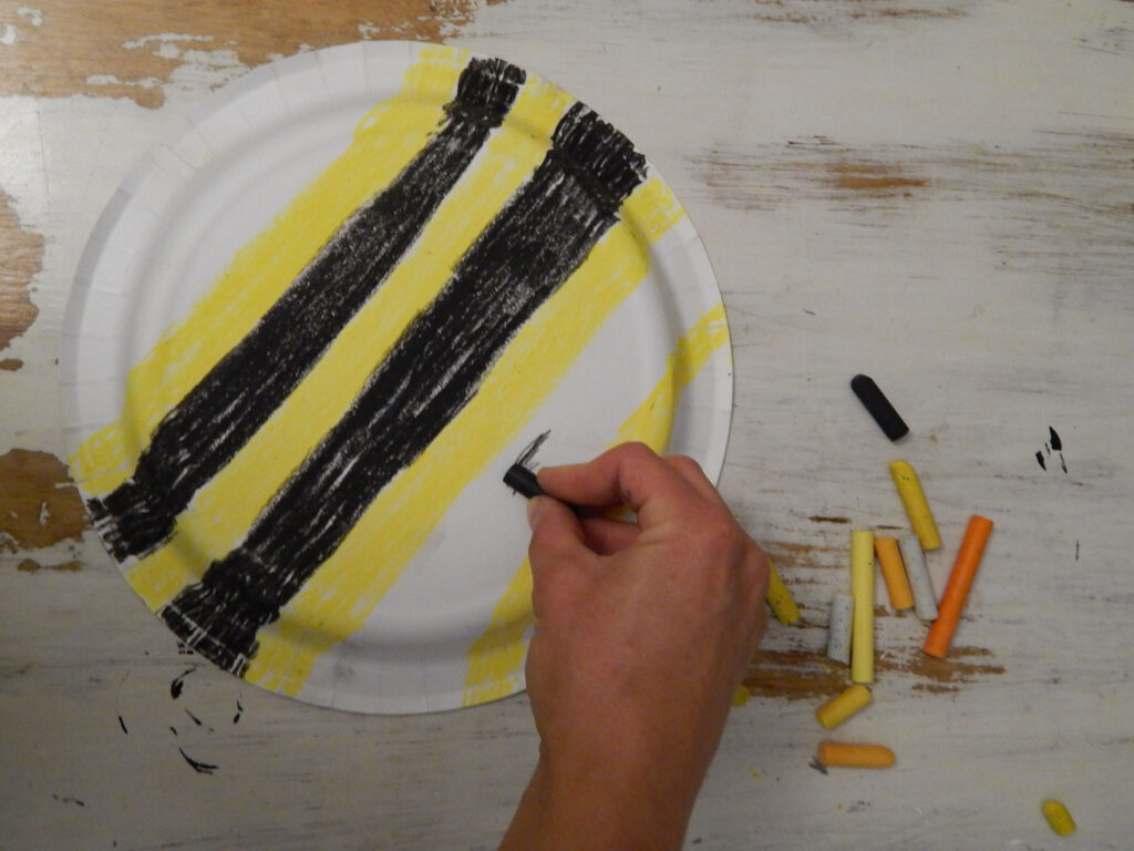 hand holding a black oil pastel coloring bumble bee stripes on a paper plate bee craft for kids