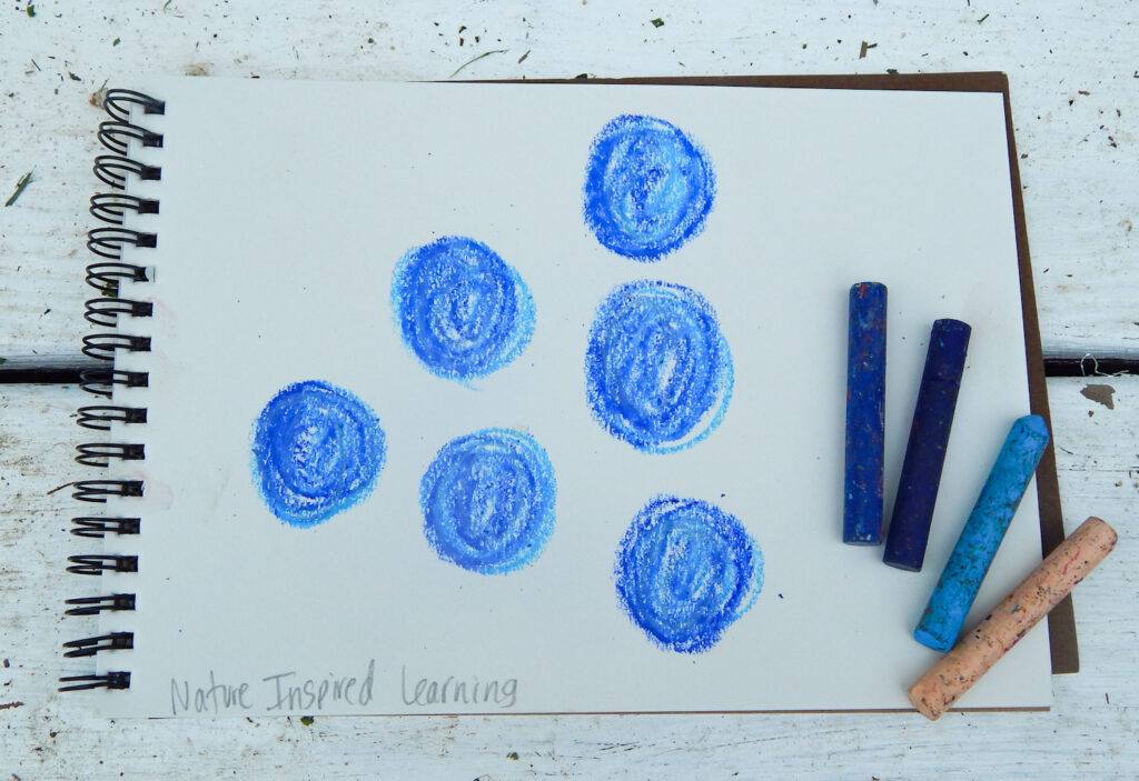 6 blueberries drawn using oil pastels in a spiral bound notebook on a dirty white step with 4 oil pastels on the side of the notebook