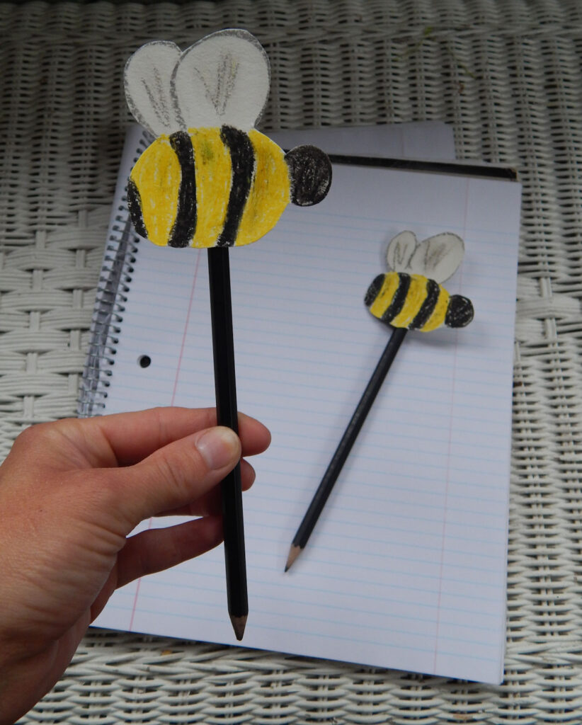 cute little bumble bees added to the top of a pencil being held by a girl's hand easy bee craft for kids made out of paper