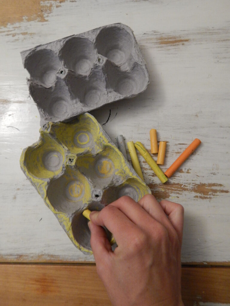hand holding a yellow oil pastel coloring an egg cartoon for a bee craft on a wooden table