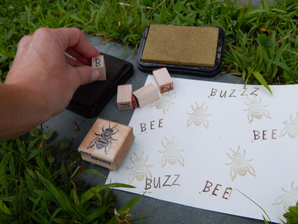 a hand stamping a letter stamp onto a dark brown ink pad bee stamp, letter stamps, stamped artwork and gold stamp pad outside in the grass