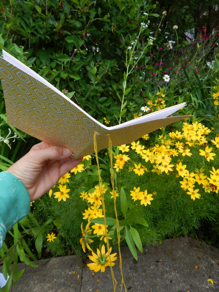 hand holding a homemade nature journal diy project outside in garden flowers blooming