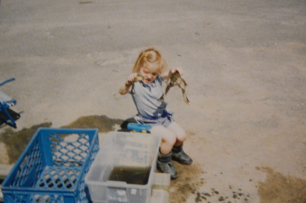 Julie from nature inspired learning as a child holding 2 frogs caught in the pond while sitting on a chair near a bin of muddy water
