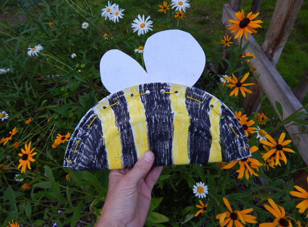 hand holding a paper plate bee craft for kids outside in the garden daisies and black eyed susans in background