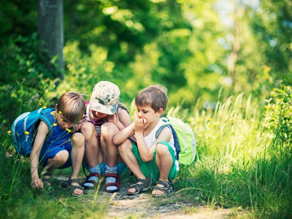 three children outside in the summer near the ground looking at the dirt and grassy walkway greenery in background