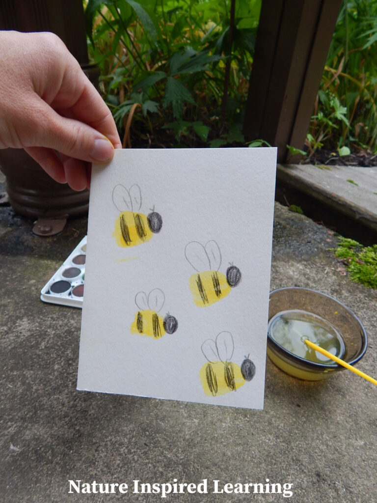 hand holding up a finished bumble bee thumb print craft homemade greeting card outside in garden