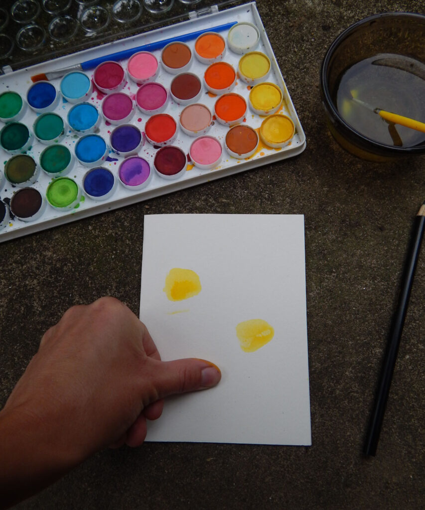 thumb pressed against DIY bumble bee greeting card yellow watercolor with watercolor paints and brush in background