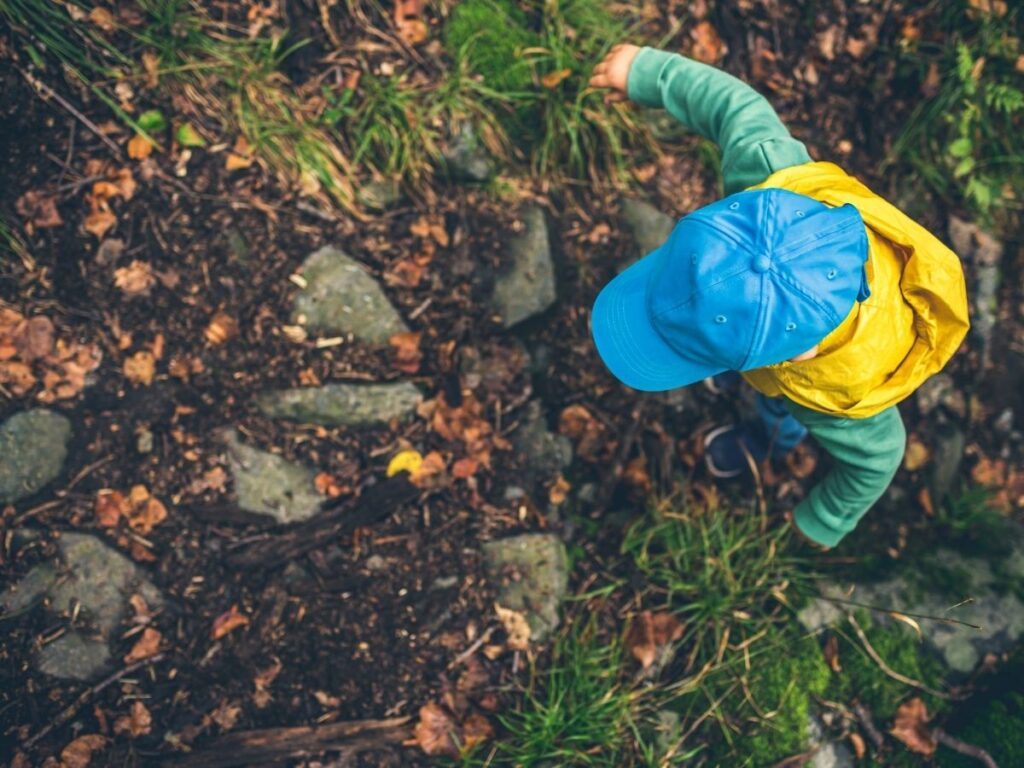 toddler on a hike wearing a bright blue hat, yellow vest, and green long sleeve shirt
