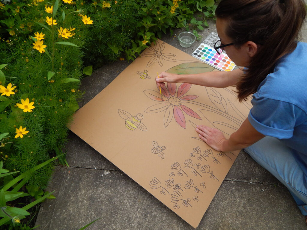 girl using watercolor paint to color in a bee garden scene outside in the garden