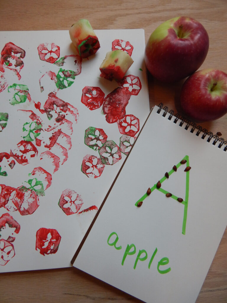 DIY apple stamping craft with apple core stamps created with red and green paint, A is for apple activity with apple seeds on the uppercase letter A with two apples on a wooden table