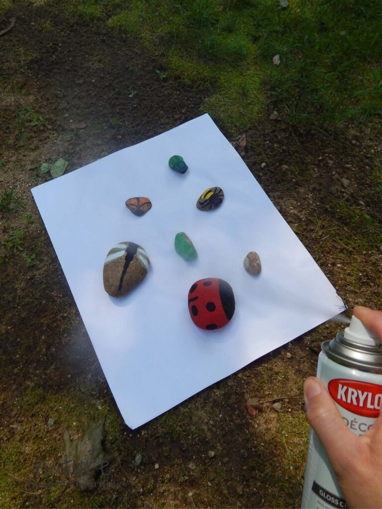 Krylon crystal clear gloss sealant being sprayed on insect painted rocks outside in the shade dragonfly painted rock, lady bug painted rock, moth painted rock, caterpillar painted rock, bee painted rock, butterfly painted rock, and click beetle painted rock on paper