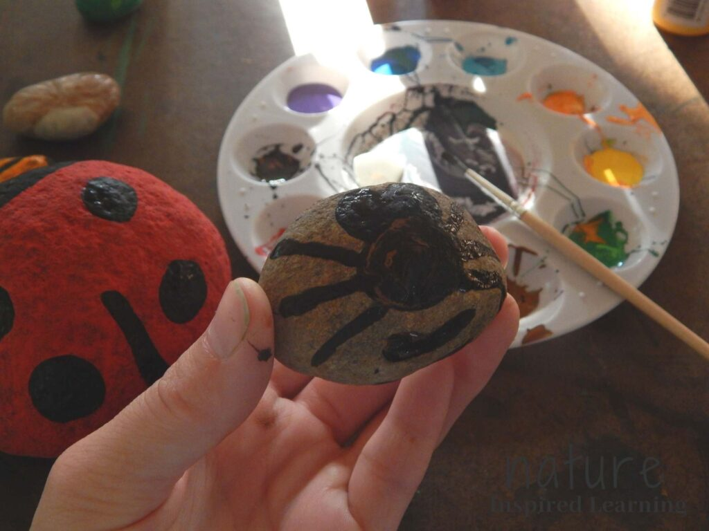 hand holding a bee painted rock with black paint on the rock ladybug painted rock on table with moth painted rock paint tray with a variety of acrylic paints on the tray with a paint brush with black paint resting on tray yellow acrylic paint bottle in top corner