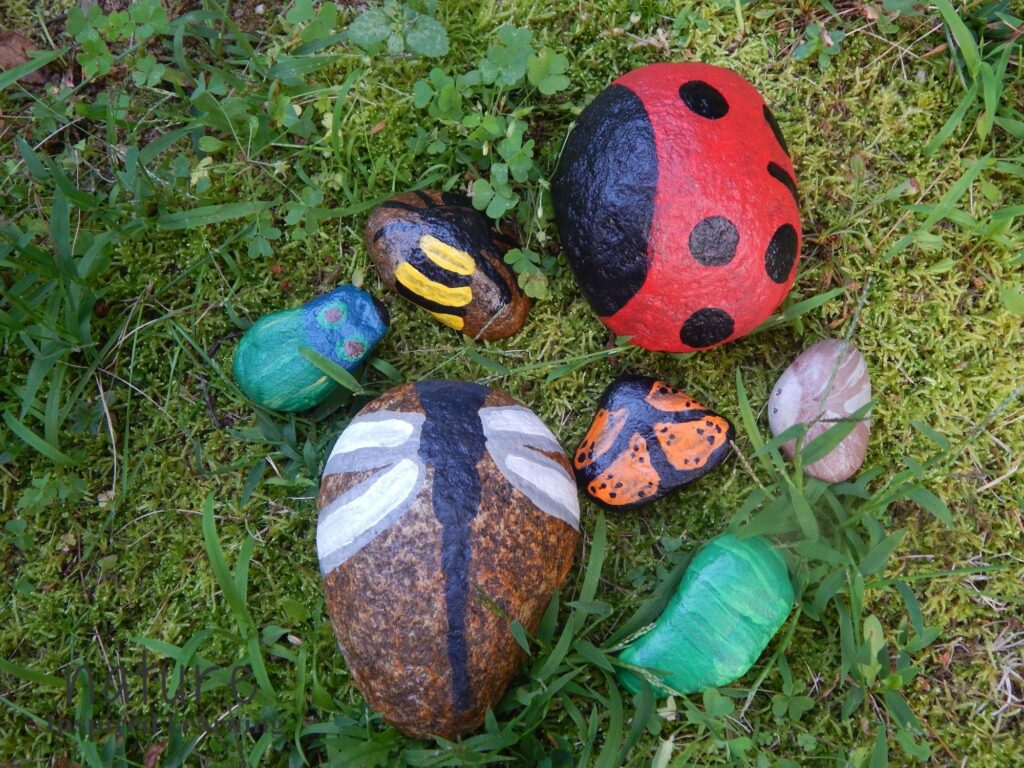 ladybug painted rock, bee rock painting, beetle painted rock, dragonfly rock art, butterfly painted rock, moth painted rock, and caterpillar painted rock outside in the grass, moss, and clover garden