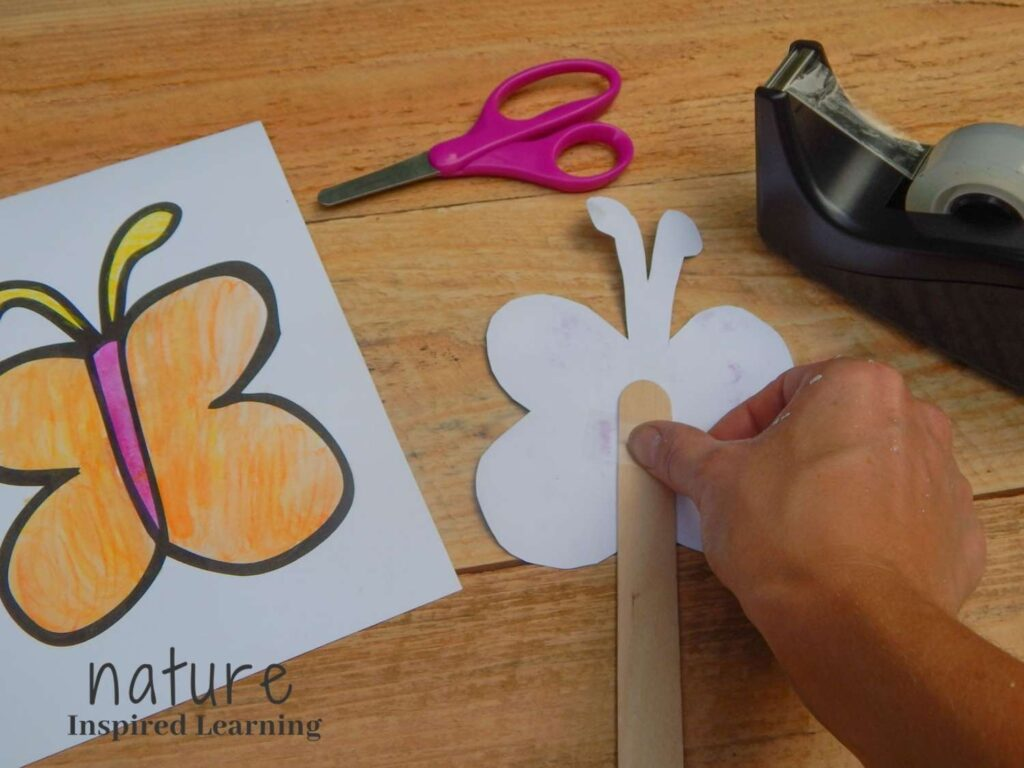 hand adding clear tape to the back of a butterfly template to create a butterfly paper craft pink safety scissors, clear tape in a black tape dispenser, colored in butterfly coloring page on wooden surface text nature inspired learning bottom corner