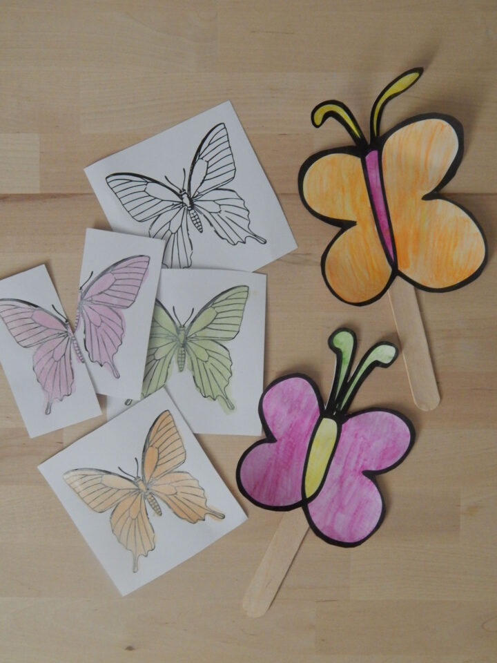 free butterfly coloring page turned into butterfly cards cut out and coloring in using paint on a wooden table next to two paper butterfly crafts made with butterfly printables painted in with pink, orange, yellow, and green watercolor paint
