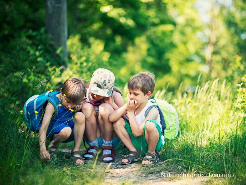three children outside wearing summer clothes on a dirt path with overgrown grass looking at the ground