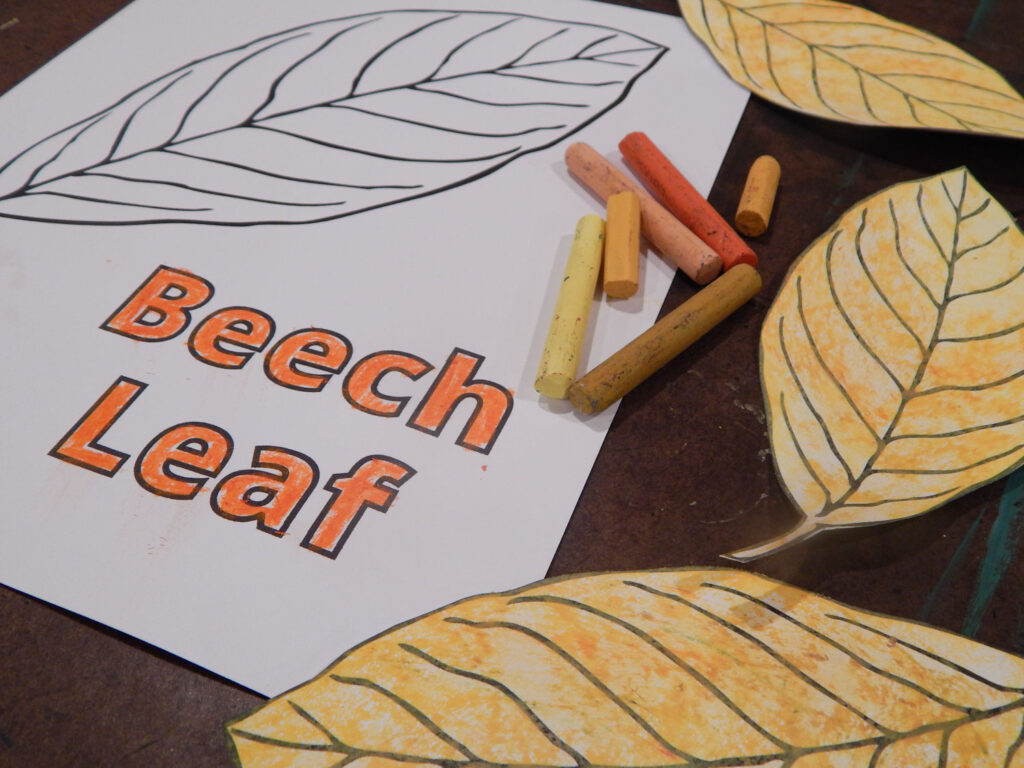 beach leaf coloring page with yellow, orange, and tan oil pastels, with three colored and cut out leaves on a table