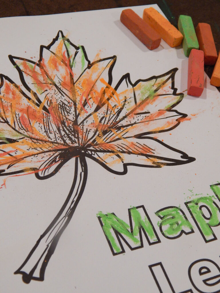 maple leaf coloring page colored in with orange and green pastels with art supplies in upper corner