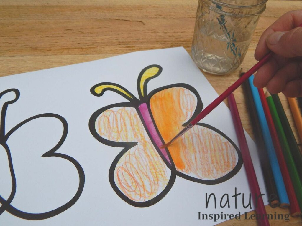 hand using a paint brush to turn watercolor pencils into paint on a butterfly coloring sheet outside on a wooden surface extra supplies to the side with text nature inspired learning bottom corner