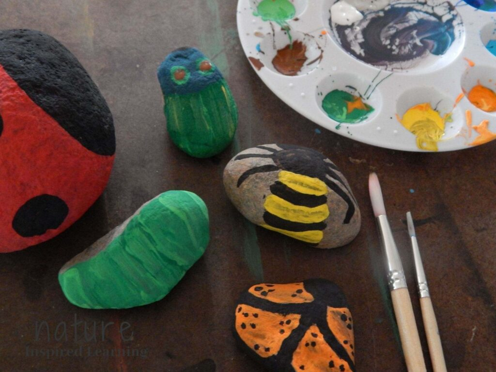insect painted rocks on a table, butterfly painted rock, bee rock painting, caterpillar painted rock, beetle painted rocks with two paint brushes and acrylic paint in a paint tray