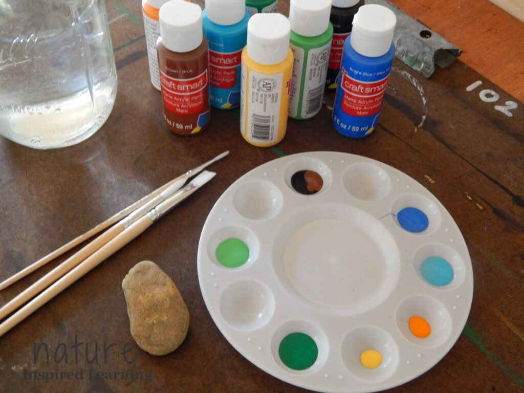 insect painting rock supplies on a board on a table, one rock, one paint tray with blue paint, orange paint, yellow paint, dark green paint, light green paint, black paint and brown paint with acrylic paint bottles a glass jar with water and three wooden paint brushes