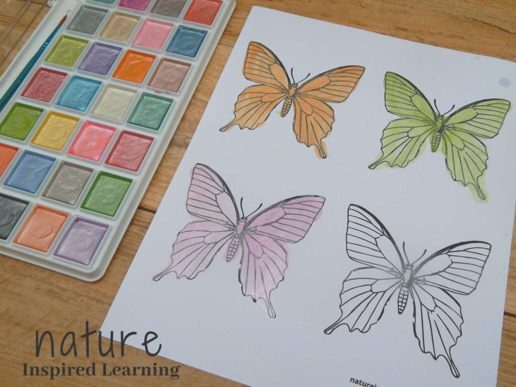 butterfly coloring sheet colored in using matallic watercolor paint paint set next the the sheet with the text nature inspired learning in bottom corner
